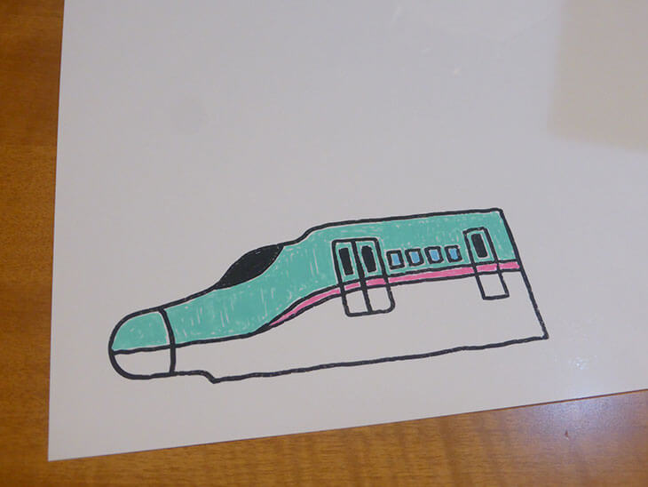 おもちゃの新幹線を描いて色を塗った白いプラバン