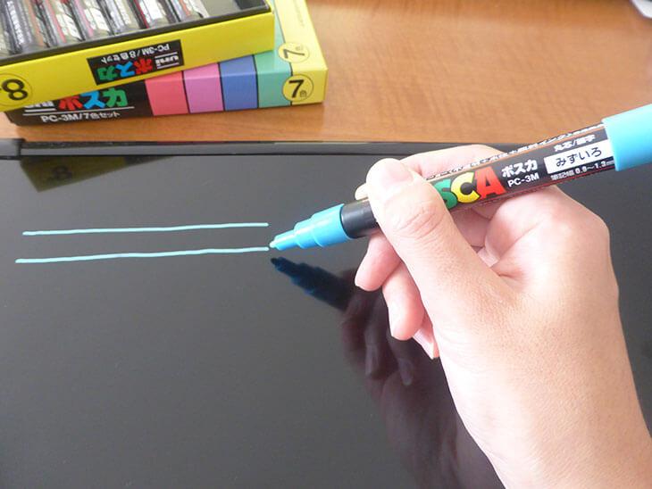 ポスカでブラックボードにプラバンおもちゃ用の絵を書いている様子
