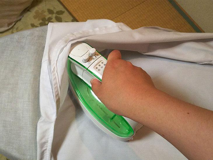 給食の白衣の後ろ身ごろを内側からアイロンがけする様子