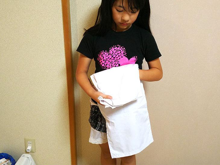 給食の白衣を折りたたむ小学生