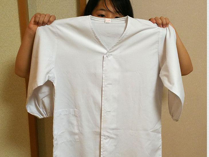 給食の白衣を持つ子供