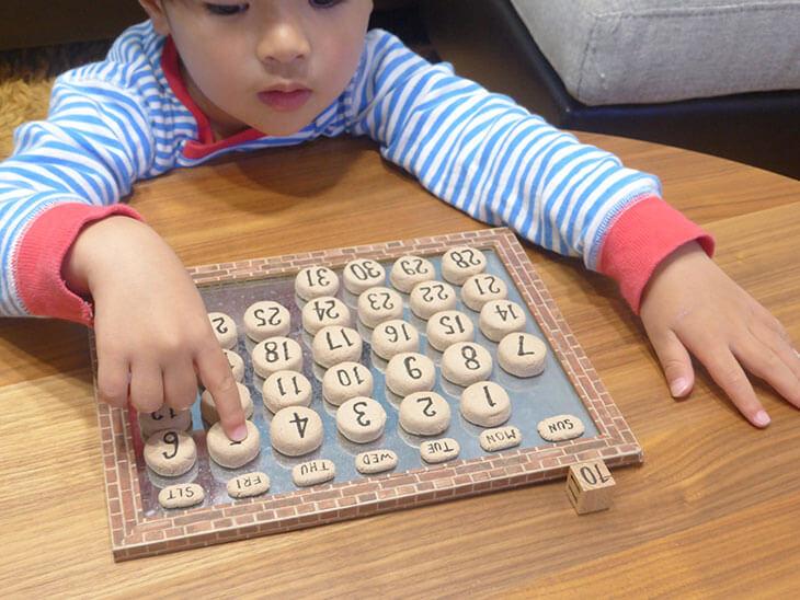 子供が完成した万年カレンダーを指さしている様子