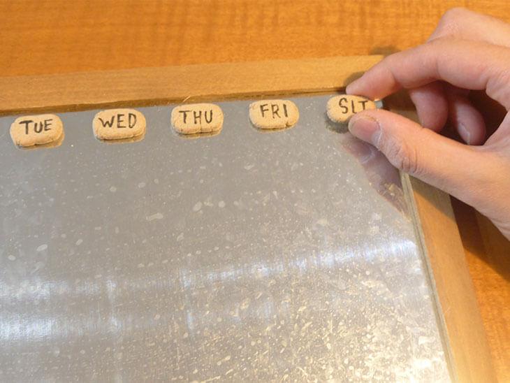 ブリキボードの上に曜日を描いた粘土を貼っている様子