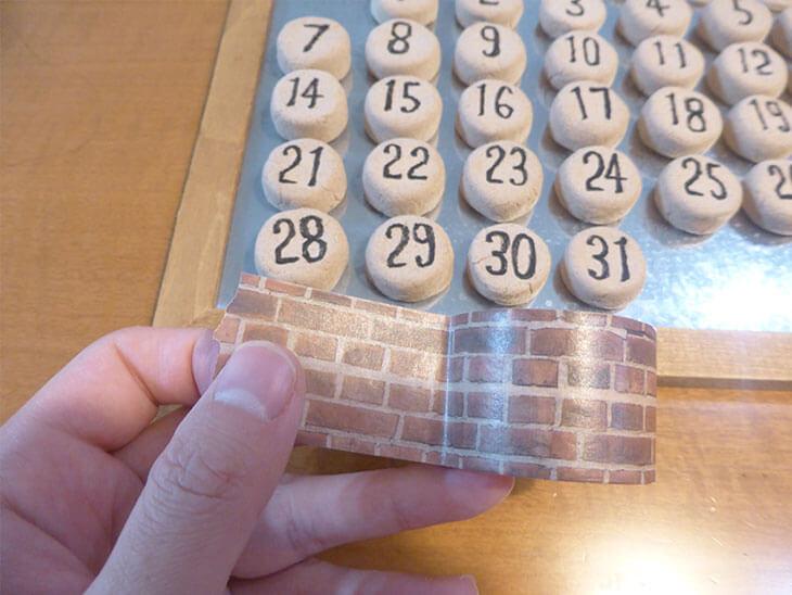 手に持ったレンガ柄のマスキングテープと作成中の万年カレンダー