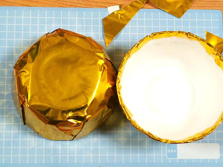 カップ麺のカップを金色の包装紙で覆って完成したくす玉の玉