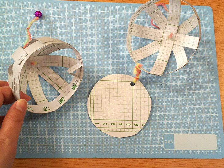 カップを毛糸で結んでくす玉を組み立てる様子