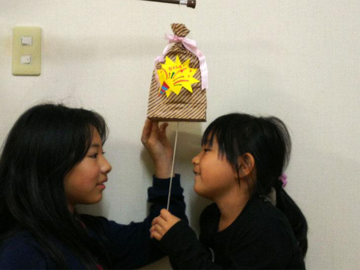 ピニャータ風紙袋のくす玉を割ろうとする子供の写真