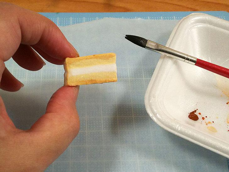 ショートケーキのスポンジ部分に絵の具で焼き色を着ける様子