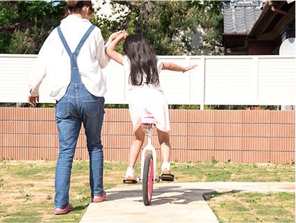 一輪車を練習する親子