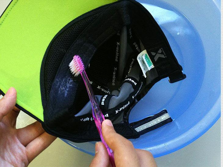 歯ブラシで帽子の汗取り部分を擦って洗濯する様子