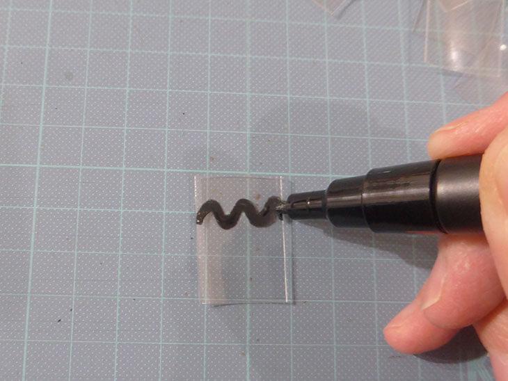ペンでペットボトル片に模様を描いている様子