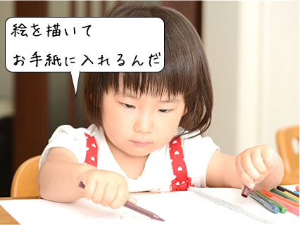 色鉛筆で手紙に絵を描く女の子