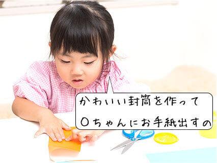 折り紙で封筒を作る女の子の幼稚園児