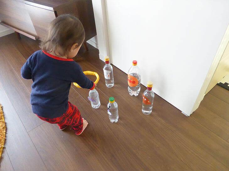 ペットボトル工作で作った輪投げで遊んでいる幼児