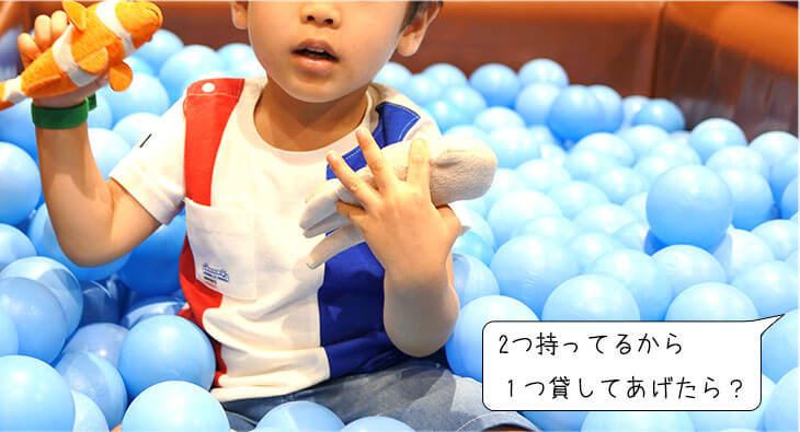 室内遊び場で2つのおもちゃを持つ男の子