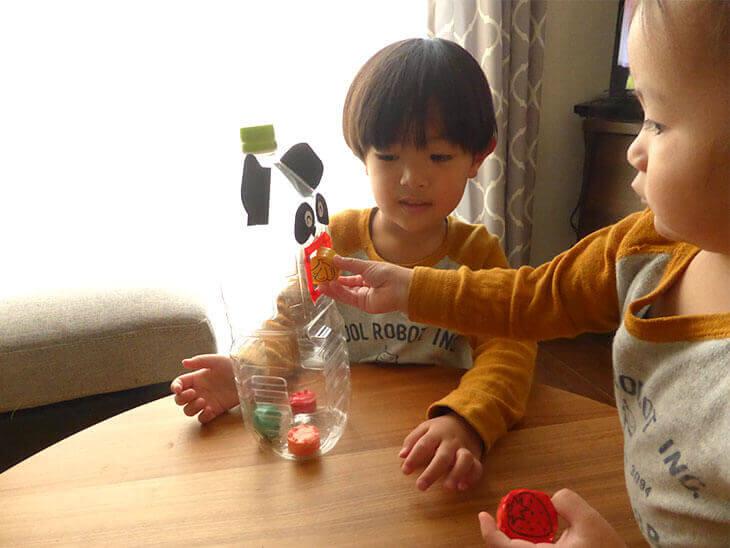 ペットボトルのパクパクパンダおもちゃで遊んでいる兄弟