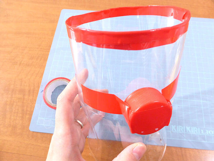 赤いテープでペットボトルにキャップを貼った様子