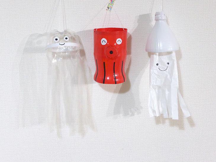 白い壁に吊るさたペットボトル工作のクラゲとタコとイカ