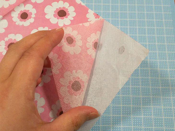柄のついた紙をペーパーナプキンの層からはがす様子