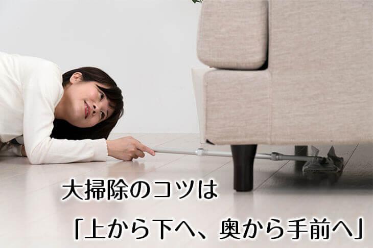 ソファ下のほこりを掃除する女性