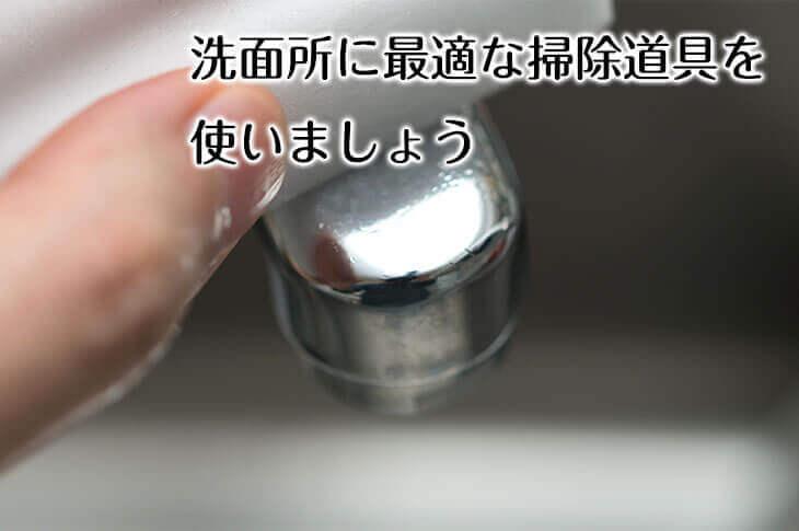 メラミンスポンジで洗面所の蛇口を掃除する主婦の手