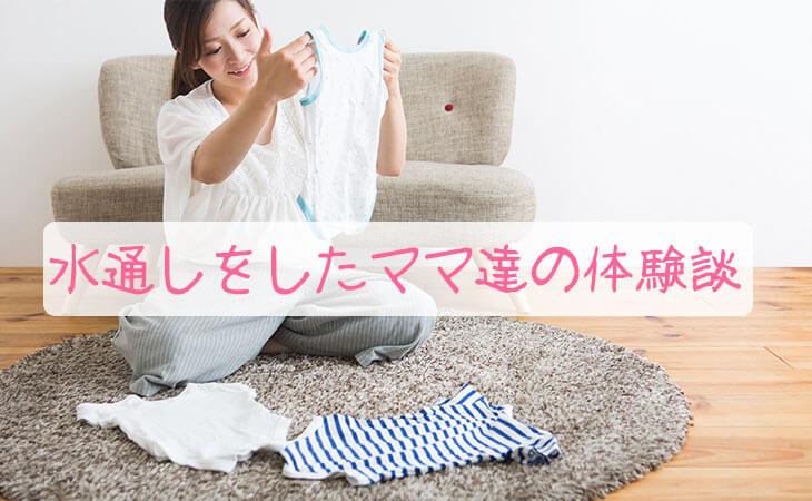 居間で赤ちゃんの服を見るママ