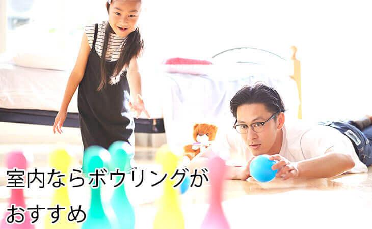 室内でボウリングをする父親と女の子の幼児