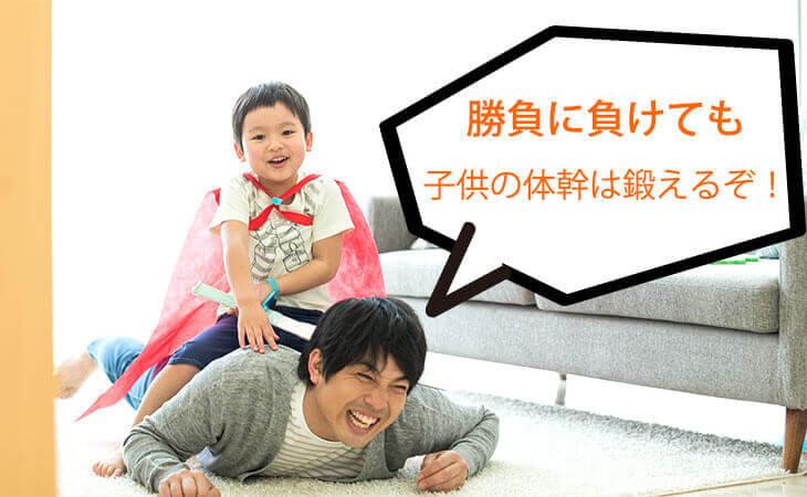パパの背中にまたがる男の子の幼児