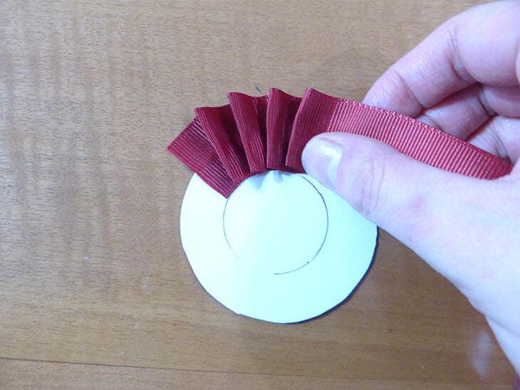 ロゼットの台紙に描いた円に合わせてリボンをじゃばらに貼る様子