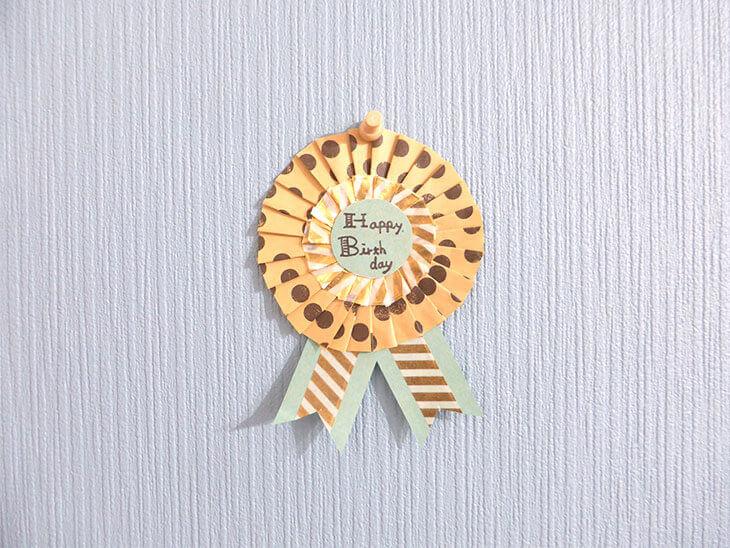 壁に飾った折り紙製の簡単ロゼット