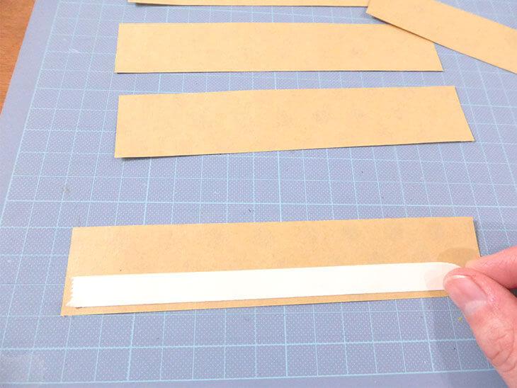 切った折り紙の裏に両面テープを貼っている様子