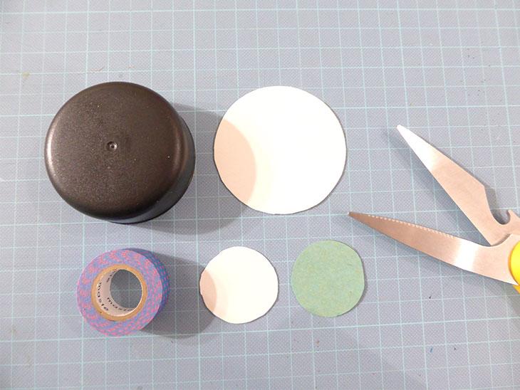 丸くカットした厚紙や折り紙と使用した丸い物やハサミ