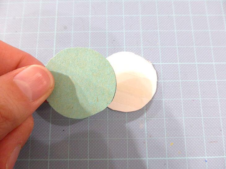 丸く切り取った厚紙に折り紙を貼る様子