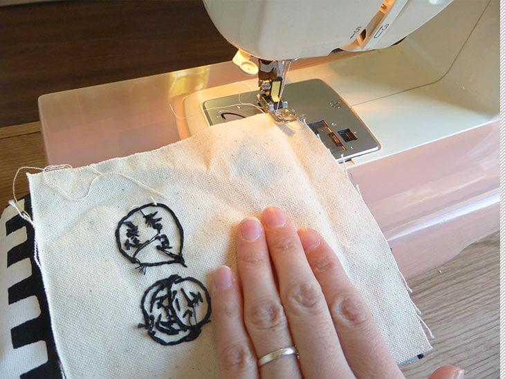 刺繍してある生地と柄の生地をミシンで縫っている様子