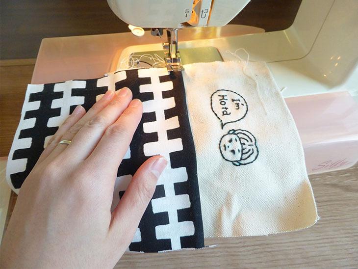 財布生地の表側をミシンで縫う様子