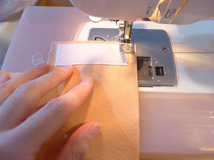 ミシンでマジックテープをフェルトに縫いつける様子