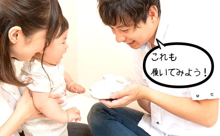 赤ちゃんに靴を試し履きさせる両親
