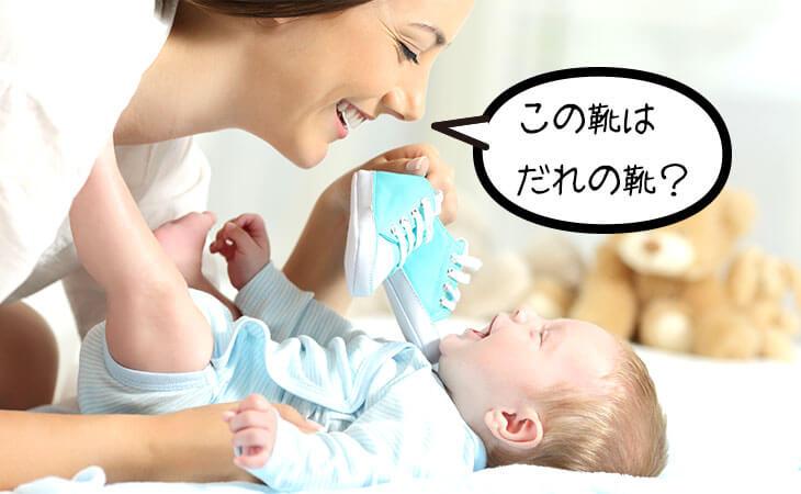 靴で赤ちゃんと遊ぶ母親