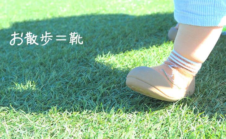 芝生の上をソックスシューズで歩く赤ちゃんの足元
