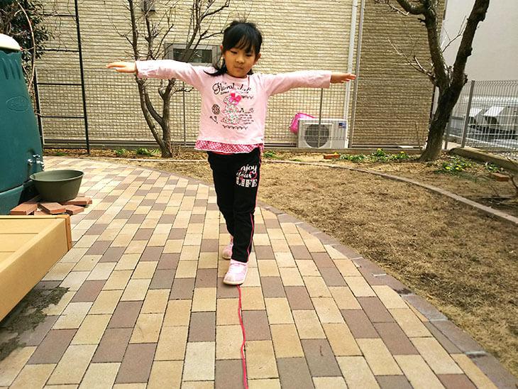 縄跳びで一本橋チャレンジをして遊ぶ幼児
