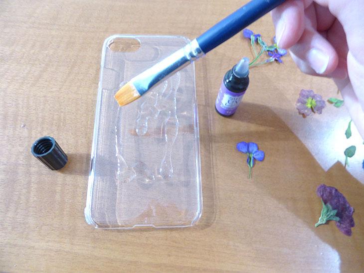 iPhoneケースに筆でレジンを塗る様子