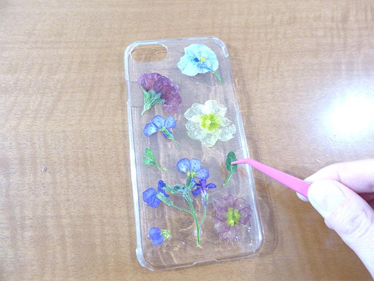 レジンを塗ったスマホケースの上に押し花を並べる様子