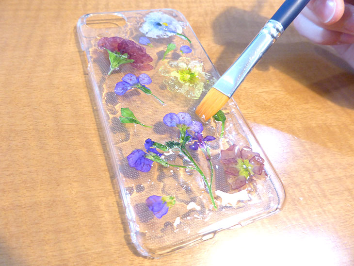 仕上げのレジンを押し花iphoneケースの上に塗る様子