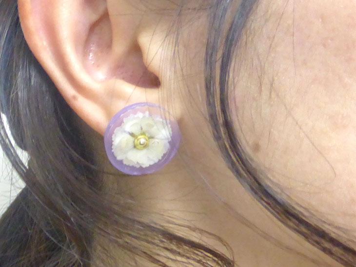 耳につけた完成した押し花のレジンピアス