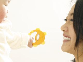 赤ちゃんをだっこして笑っているお母さん