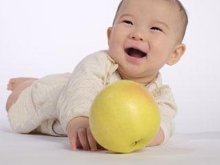 りんごとあそぶ笑顔の赤ちゃん