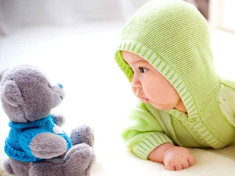 暖かい服を着る赤ちゃんとクマのぬいぐるみ
