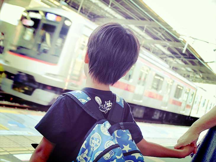 母親と一緒に電車で旅行に行こうとしている男の子