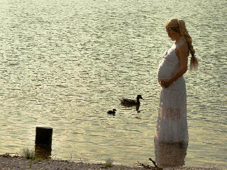 水辺に立つ妊婦