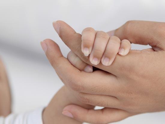 赤ちゃんの手を握る親